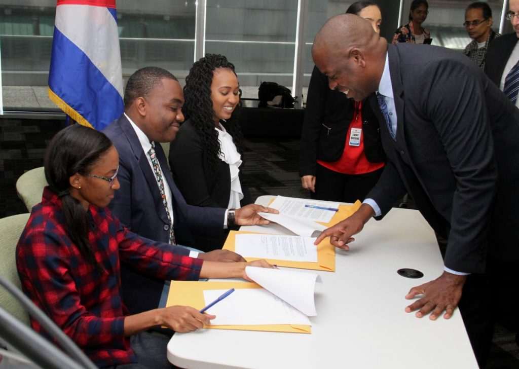 Minister in the Ministry of Education Lovell Francis with Cuba scholarship recipients, from left, Andrea Branche, Manasseh Mark and Radannia Picou as they sign the code of ethics at the Cuban scholarship signing ceremony at the Education Towers, Port-of-Spain on Friday. PHOTO BY AYANNA KINSALE