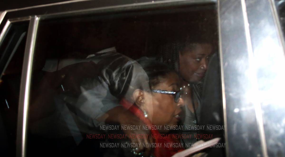 Public Administration Minister Marlene McDonald, left, is being taken away from the Professional Standards Bureau on Henry Street in Port of Spain in a heavily tinted police SUV on Friday night. PHOTO BY SUREASH CHOLAI