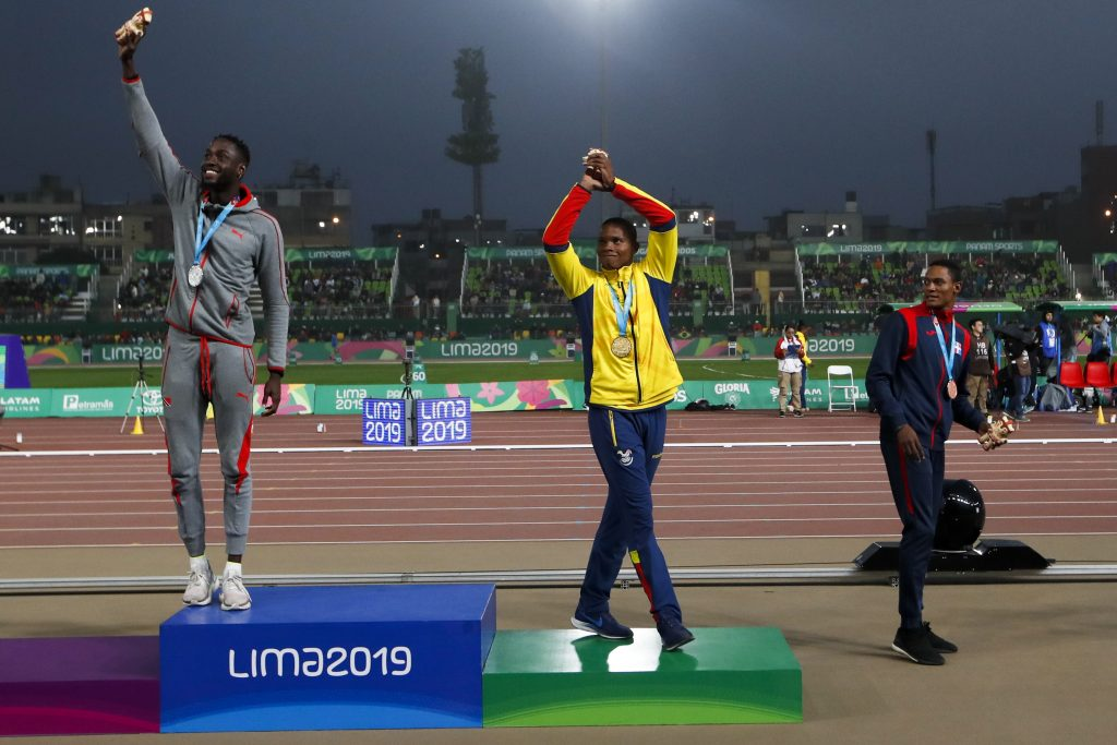 Silver medalist Jereem Richards ofTrinidad and Tobago, right, walks away as gold medalist Alex Quinonez ofEcuador, center, and bronze medalist Yancarlos Martinez ofDominican Republic celebrate on the podium for the men's 200m during the athletics at the Pan American Games in Lima, Peru, Friday, Aug. 9, 2019. (AP Photo/Moises Castillo)