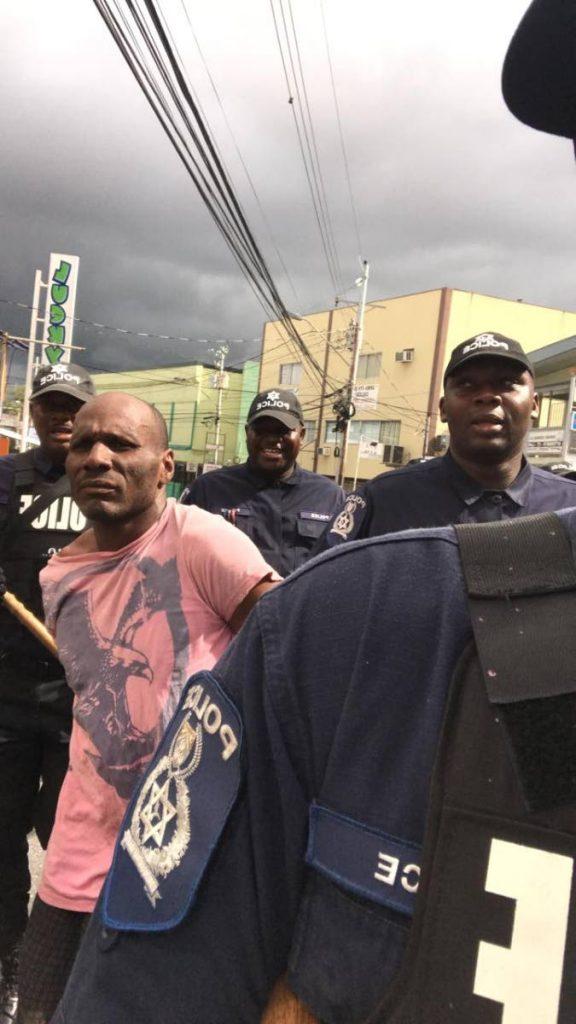 Police take prison escapee Dillon Clarke into custody on Hollis Avenue, Arima during borough day celebrations on Saturday. PHOTO SOURCE SOCIAL MEDIA