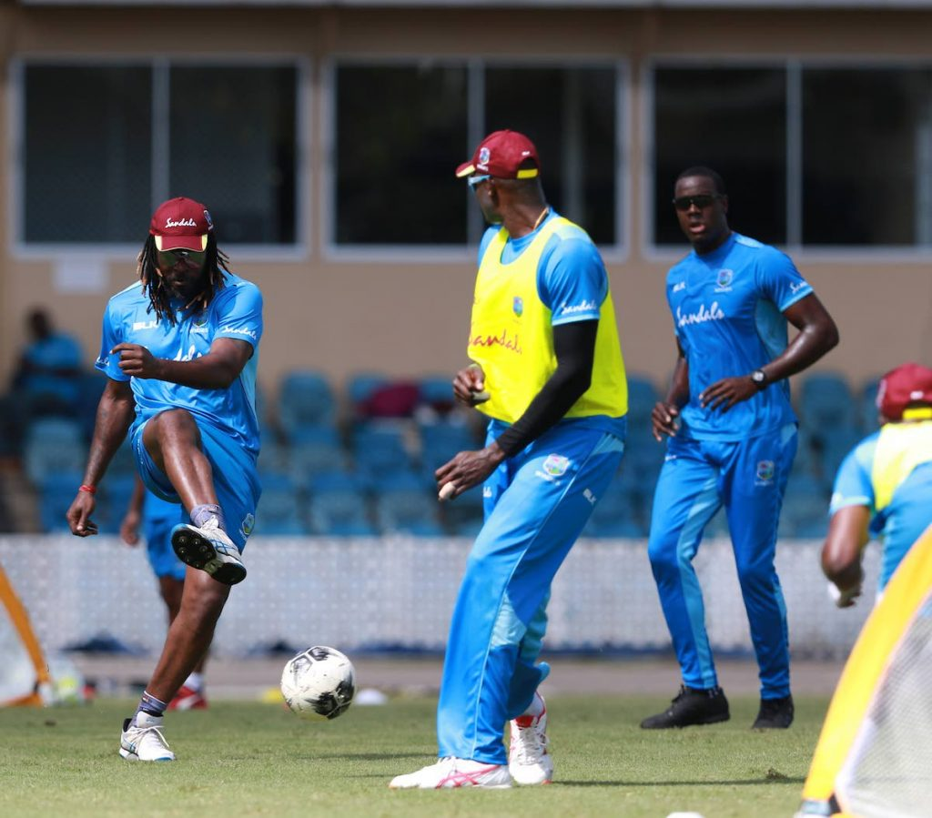 West Indies' Chris Gayle fires a shot while captain Jason Holder (centre) defends during a warm-up football game at the Queen's Park Oval, St Clair yesterday. Also in photo is all-rounder Carlos Brathwaite (right).