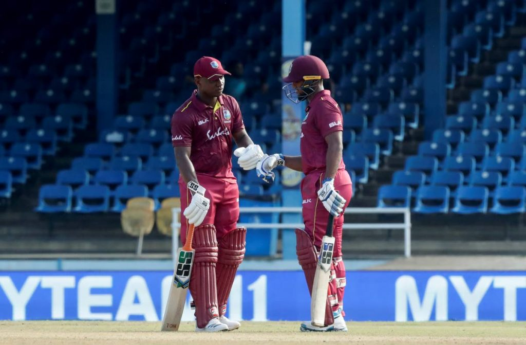 West Indies Evin Lewis (left), knocks his glove with batting partner Nicholas Pooran during their second One-Day International against India at the Queen's Park Oval on Sunday. (AP PHOTOS)