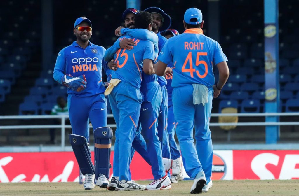 India bowler Bhuvneshwar Kumar (centre) is hugged by captain Virat Kohli after dismissing West Indies batsman Roston Chase during their second One-Day International at the Queen's Park Oval.