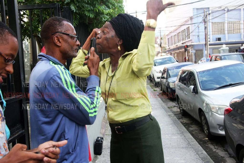 """Laventille activists Christine """"Twiggy"""" Livia, right, and  Christopher Garth argue outside the Port of Spain Magistrates Court on Monday while awaiting the arrival of Marlene Mc Donald. PHOTO BY SUREASH CHOLAI"""