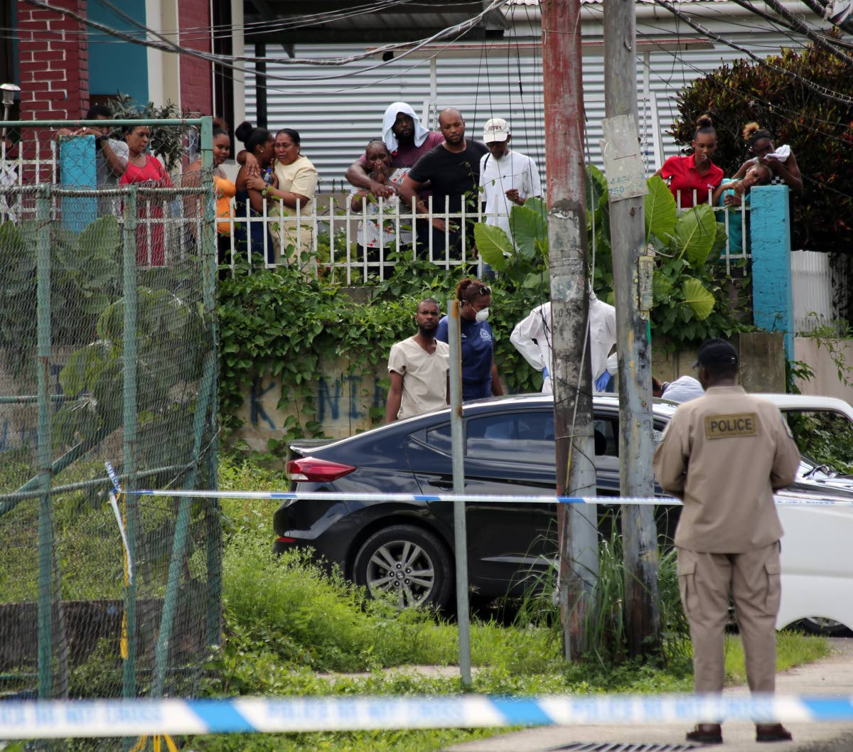"""SHOCK: Relatives look on in grief as the body of Shaquille """"Papa"""" Eugene is removed from  the car which he was driving when he was ambushed and shot at Morne Coco Road,  Maraval yesterday.   PHOTO BY SUREASH CHOLAI"""