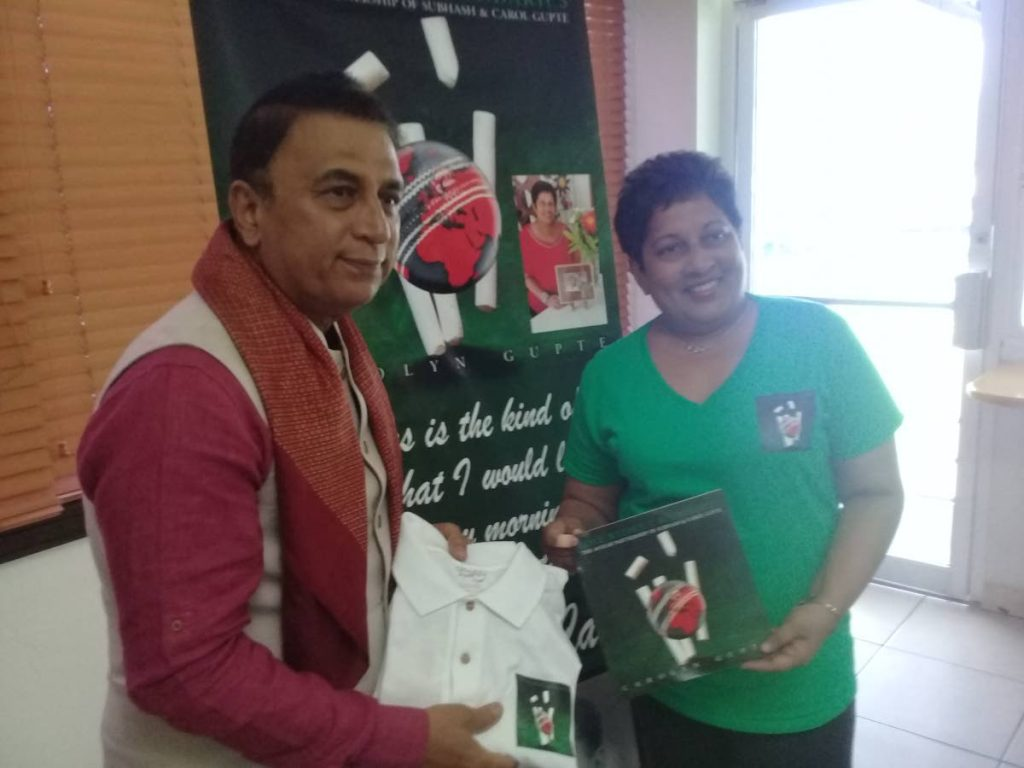 Carolyn Gupte, right, presents a book to Indian cricket legend Sunil Gavaskar at the Queen's Park Oval in St Clair, yesterday.