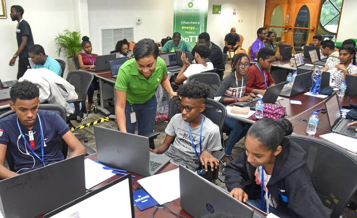 Rachael Caines, standing, corporate reponsibility advisor, BPTT, shows keen interest as these students explain what they are doing at the coding camp.