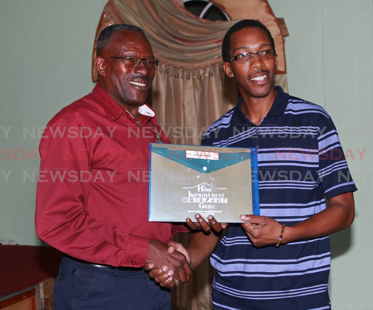 Minister of Housing and Urban Development Edmund Dillion presenting a recipient with his Grant at the Point Fortin Borough Town Hall on Wednesday.  PHOTO BY: CHEQUANA WHEELER
