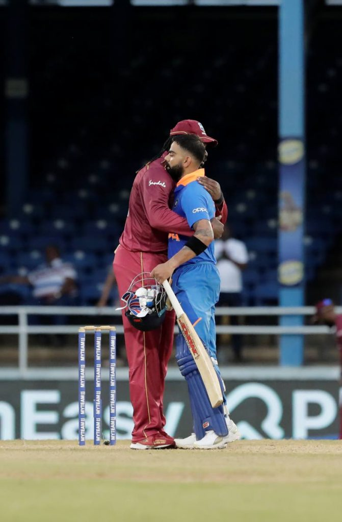 West Indies Chris Gayle (left) and India captain Virat Kohli, embrace at the end of their third One-Day International match at the Queen's Park Oval yesterday. (AP PHOTO)