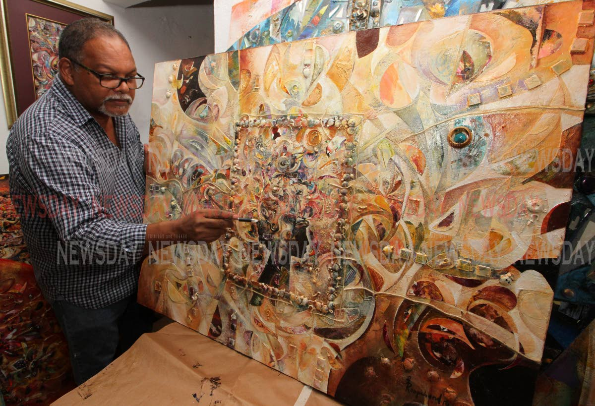 Artist Glenn Mohammed reviews his piece Vande Materam, one of his creations for his exhibition Parade. PHOTOS BY ANGELO MARCELLE