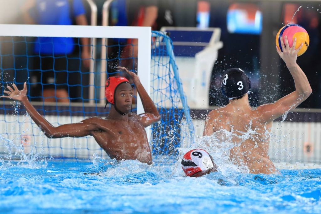 Argentina's Mateo Giri (#3) shoots and scores pas TT's goalkeeper Zaphaniah Taylor-Saodenha during the UANA Waterpolo Youth Championship at the National Aquatic  Centre, Couva,  yesterday.