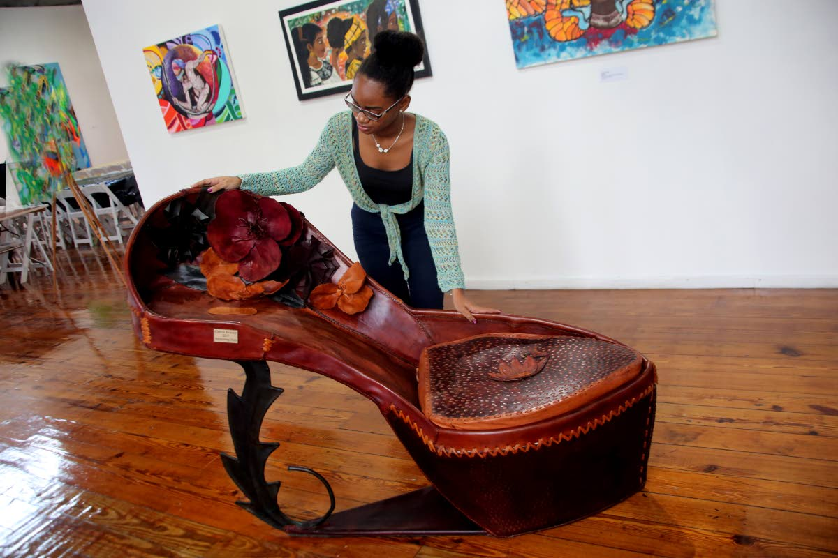 FOR A BIG FOOT: Carifesta volunteer Ebony Smith examines a work of art titled, Burgeoning Steps' by Carol Fraser at the Caricom Art exhibition yesterday at the National Museum in Port of Spain.