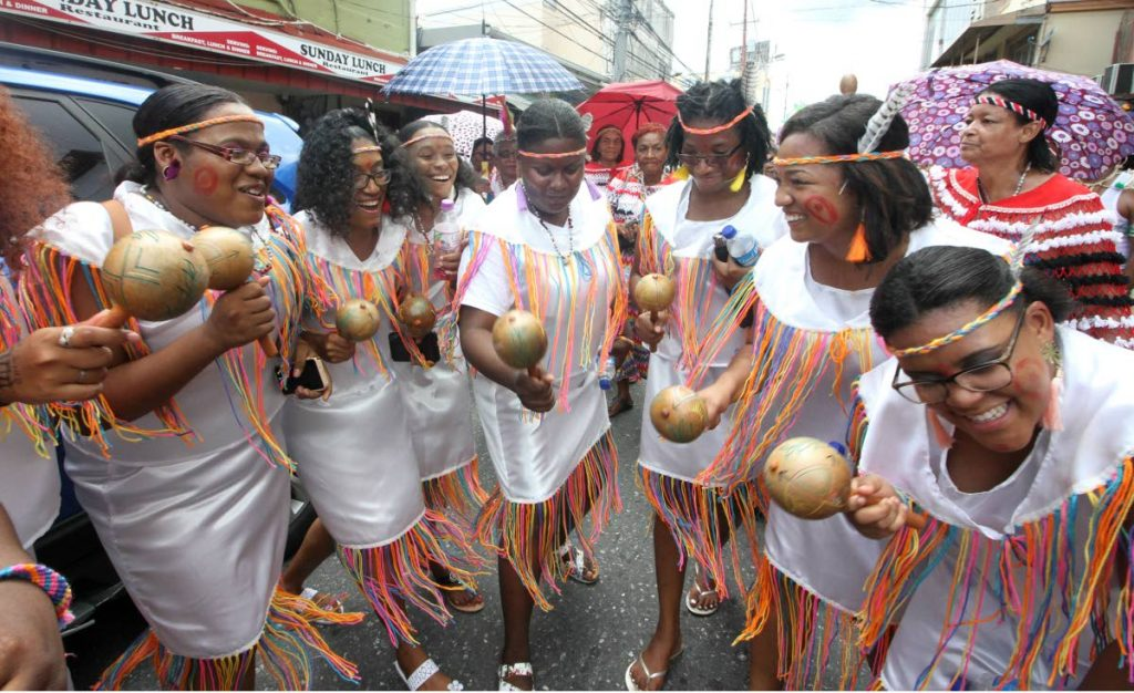 JOYFUL NOISE: Members of the Santa Rosa First Peoples Performing Company, dance and shake their maracs through the streets of Arima.