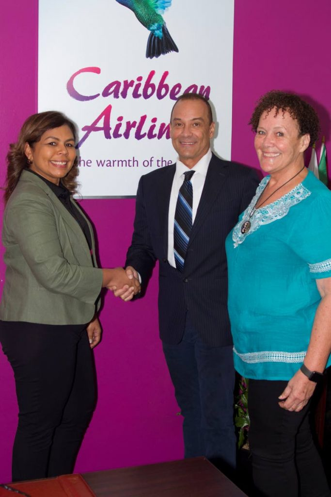 Alicia Cabrera, Executive Manager, Marketing and Loyalty, Caribbean Airlines Limited (left) shakes hands with Colin Borde (centre), Logistics Manager, Plan It Productions, at the Caribbean Airlines Piarco Head Office while Niki Borde, Event Manager, Plan It Productions, looks on.