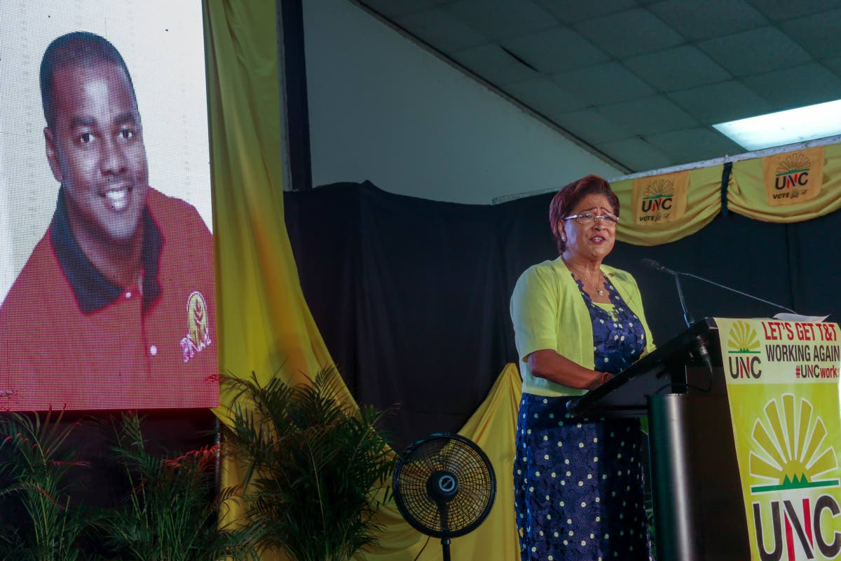 UNC political leader Kamla Persad-Bissessar speaks to supporters during a rally on Sunday at the Couva South multi-purpose complex.  Behind her on a screen is a photo of PNM senator Foster Cummings.