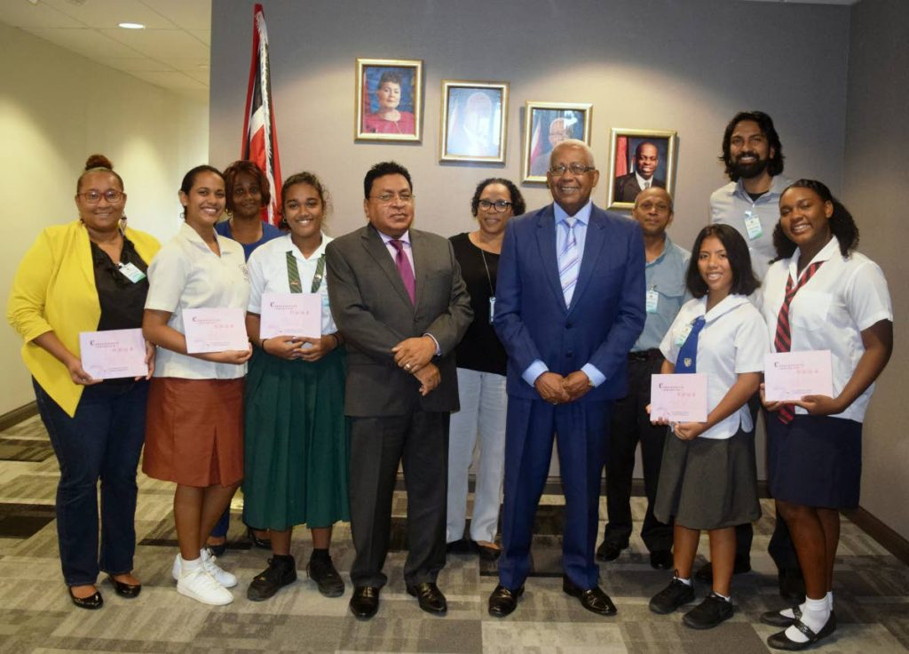 Education Minister Anthony Garcia and Chief Education Officer Harrilal Seecharan with Angelina Mia Hosein, Hsiao-Fa Lee Ha, Kayla Batchasingh and Jodi Cunningham who rticipated in the 15th Shanghai International Youth Freindship camp. Also in the picture are the students' parents.
