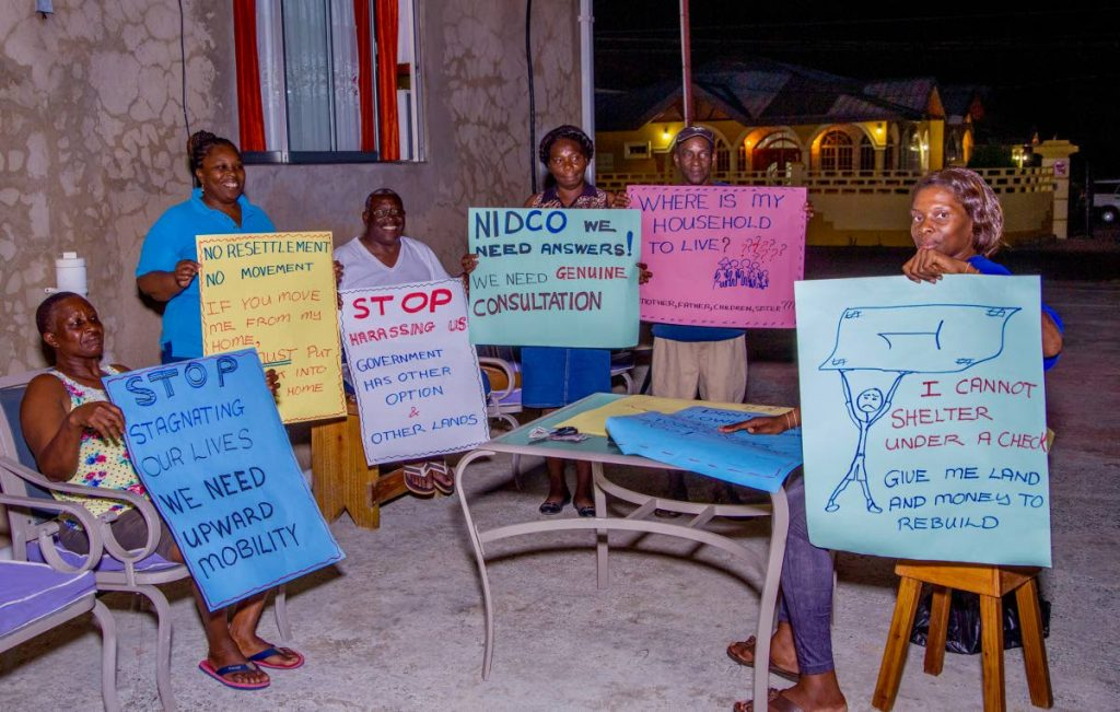 Friends and family of Horace and Beverly Henry prepare placards for a protest earlier this year. The Henrys' home at Store Bay Local Road fell in the zone affected by the airport expansion project.