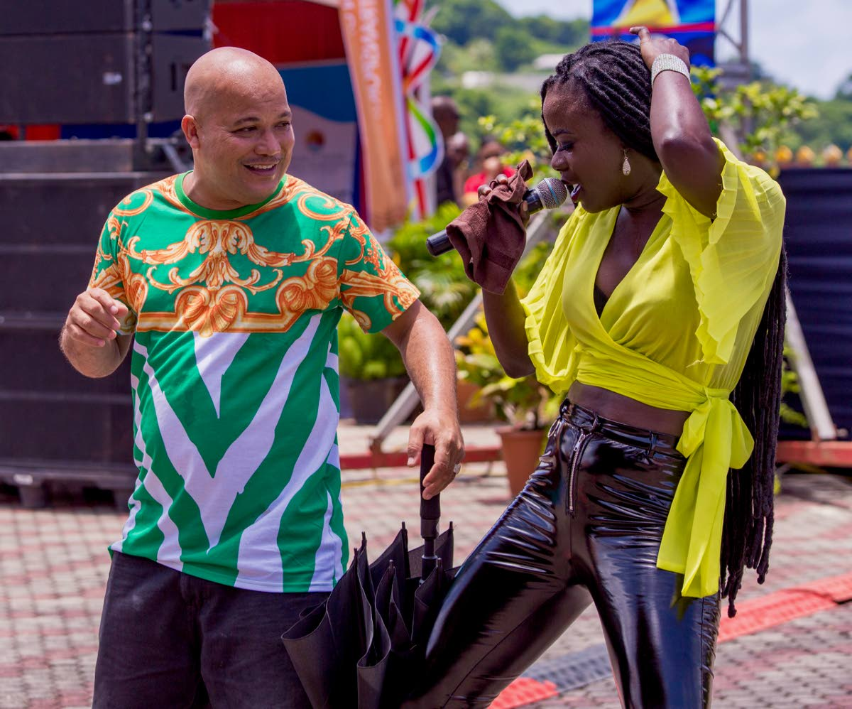 Soca singer Adana Roberts dances with a member of the audience during her performance at Scarborough Esplanade at the launch of the Carifesta Tobago Grand Market on Monday.