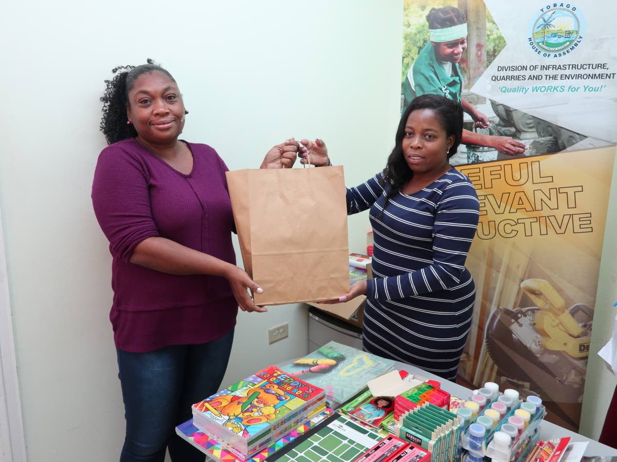 Office assistant Maria Roberts, left, collects a back-to-school package for the women's programme section at the URP head office, Shaw Park.