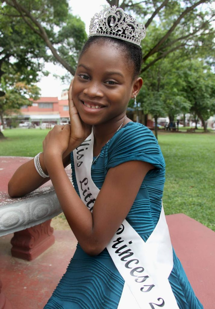 Princess goals: Miss Little Princess Celine Warner relaxes at Woodford Square, Port-of-Spain. The standard four students wants to help others as a doctor.  PHOTOS BY  AYANNA KINSALE