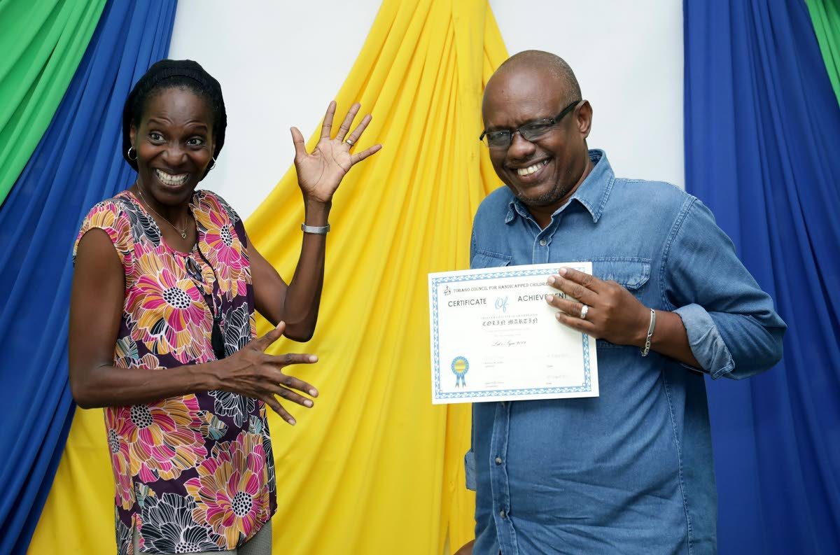 Chairman of Autism Tobago and member of the Tobago Council for Persons with Disabilities Ria Paria, left, shares a light moment with Colin Martin after presenting him with his certificate of participation during the graduation ceremony for participants of the sign language class at the Red Cross Building Signal Hill, last week.