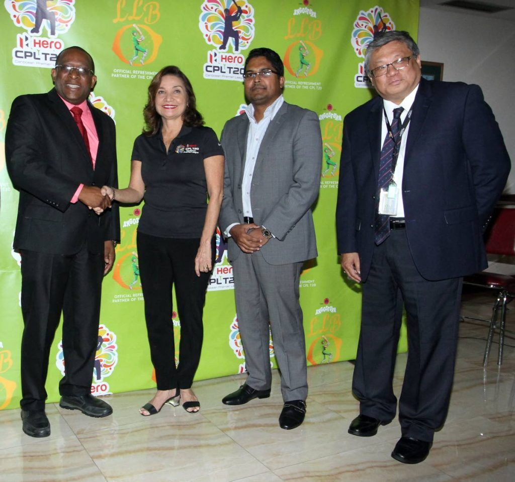 Angostura Ltd acting CEO, Ian Forbes, shakes hands with Hero Caribbean Premier League T20 Tournament, head of branding and hospitality, Natalie Black-O'Connor at a press conference to launch the partnership between Angostura and CPL at House of Angostura, Eastern Main Road, Laventille. Looking on are executive manager corporate services Rahim Mohammed, second from right, and executive manager regional sales Alejandro Santiago. PHOTO BY ANGELO M. MARCELLE