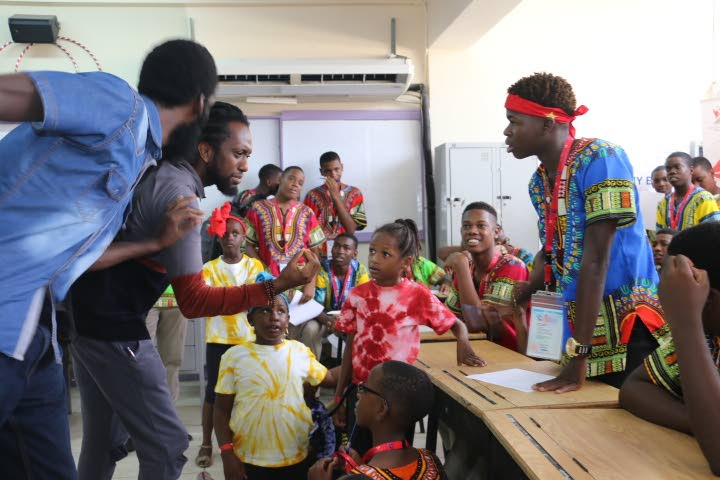 Local poets Derron Sandy and Idrees Saleem listen to improvised lines of poetry from Jarel Bartholemew of Presentation College, Grenada.