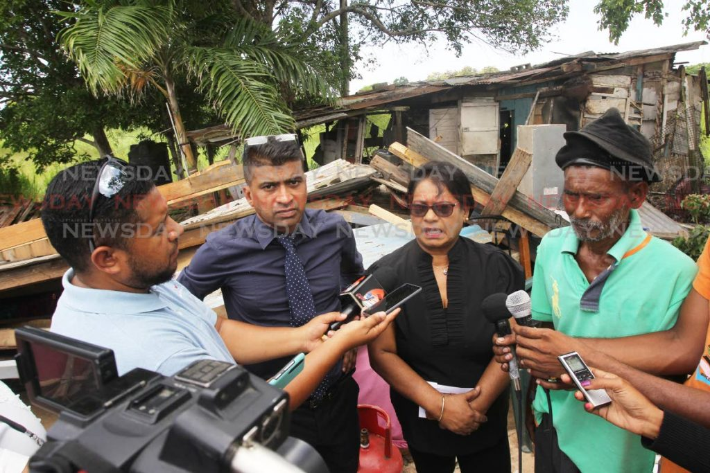 HELP NEEDED: Dr Glenn Ramadharsingh, chairman of the Siparia Regional Corporation and councillor Chanardaye Ramadharsingh with affected resident Sham Maraj in front of one of the houses.   PHOTO BY LINCOLN HOLDER