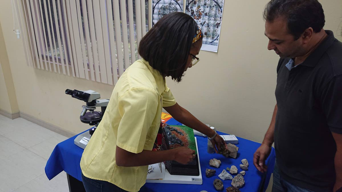 Research assistant Michal Camejo shows participant, Andre Thompson, the types of rocks formed from a volcanic eruption.