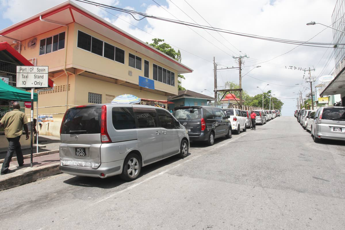 STANDSTILL: Cars belonging to taxi drivers plying the San Fernando to Port of Spain route line up on each side of the road between Library Corner and Harris Promenade in San Fernando yesterday.