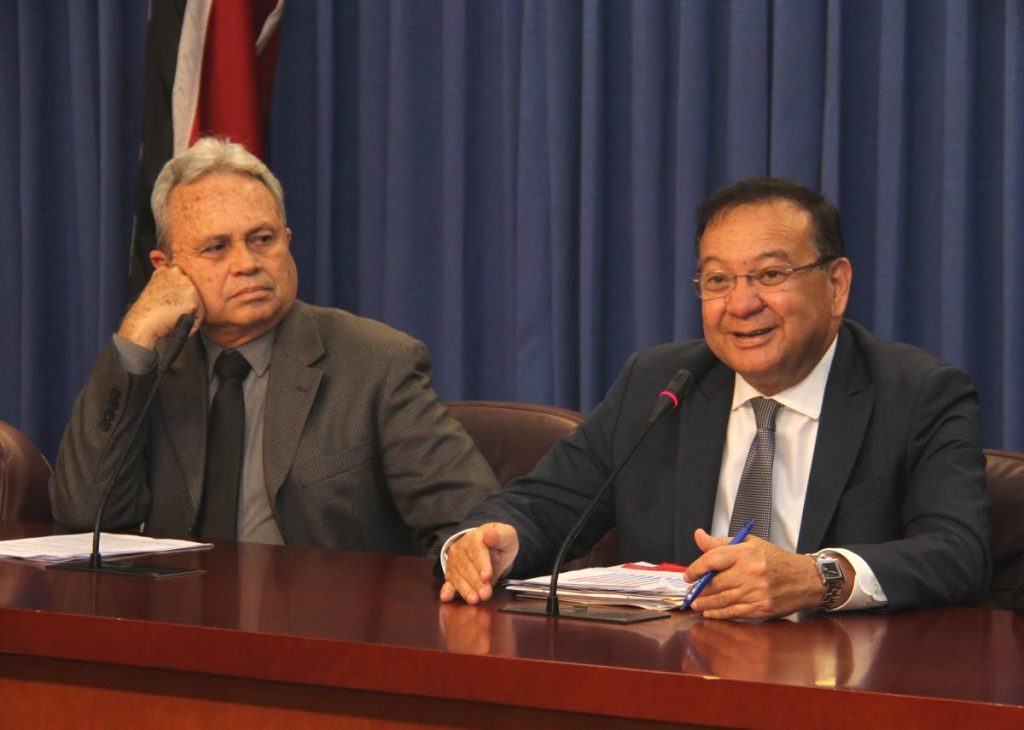 ENERGY TALK: Minister of Energy and Energy Industries Franklin Khan addresses reporters at yesterday's post-Cabinet media conference at the Diplomatic Centre in St Ann's.  Looking on is Finance Mnister Colm Imbert.