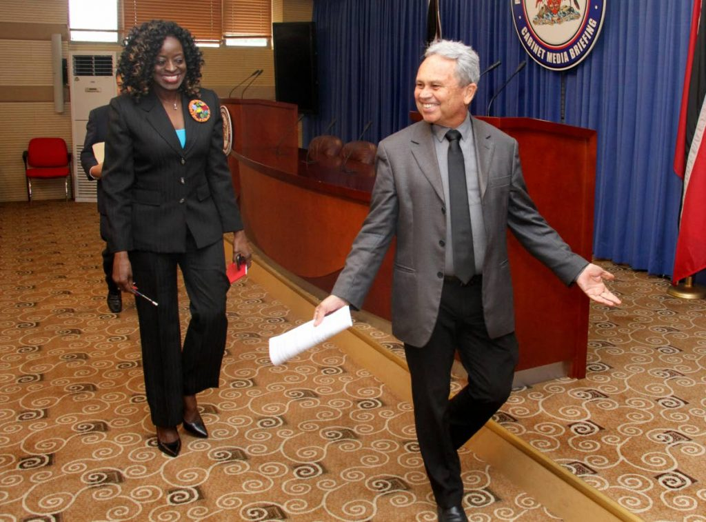 WALKING MAN: Finance Minister Colm Imbert, followed by Communications Minister Donna Cox, arrive at yesterday's post-Cabinet media briefing at the Diplomatic Centre in St Ann's.