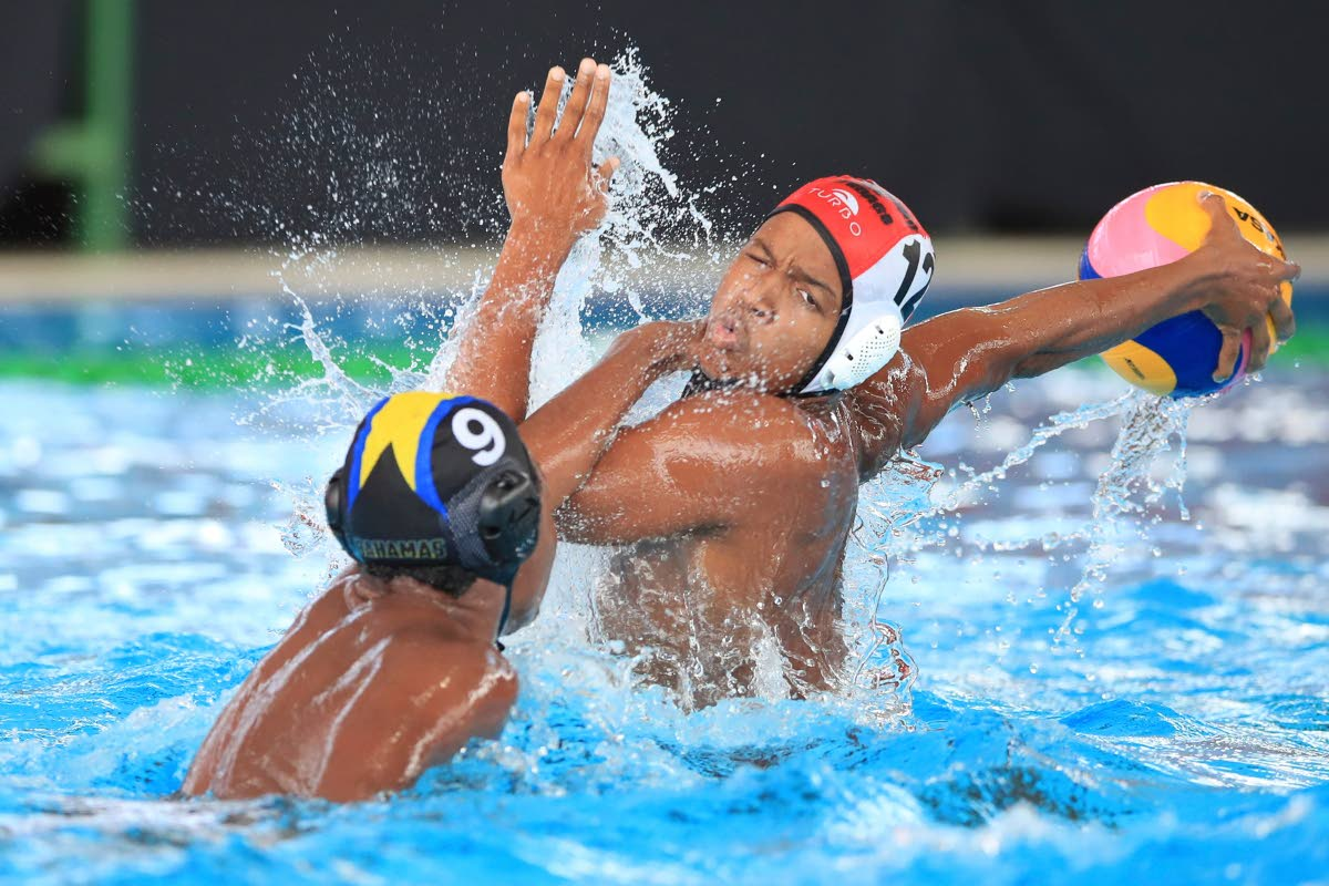 TT's Marvin Gillard-Brucs (#12) prepares to fire a shot at goal with Bahamas' Dominic Demeritte (#9) commiting a foul,during the UANA Waterpolo Youth Championship between U17 Boys TT and Bhamas at the National Aquatic Centre, Couva,yesterday. The match ended in a 9-9 draw.
