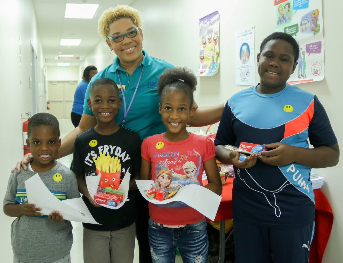 Osie Grant, from left, Thijs Foster, Amelia Mendoza and Carlton Wellington learn about caring for their teeth with a health professional at the Children Wellness Initiative, Women's Centre, Mt Hope Women's Hospital yesterday. PHOTO BY MARVIN HAMILTON