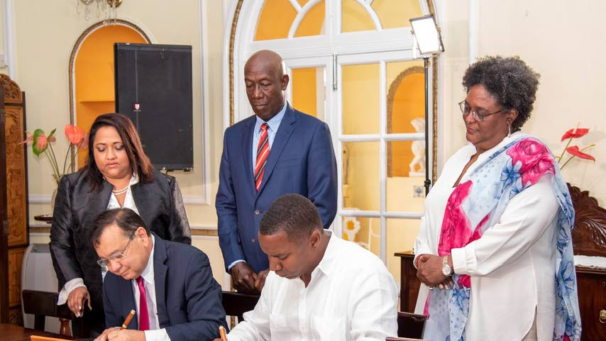 On the dotted line: Prime ministers Dr Keith Rowley and Mia Mottley observe as Energy Minister Franklin Khan (left) and his Barbados counterpart Wilfred Abrahams sign the MOU on energy cooperation in Bridgetown yesterday. Photo: Barbados PM Twitter account