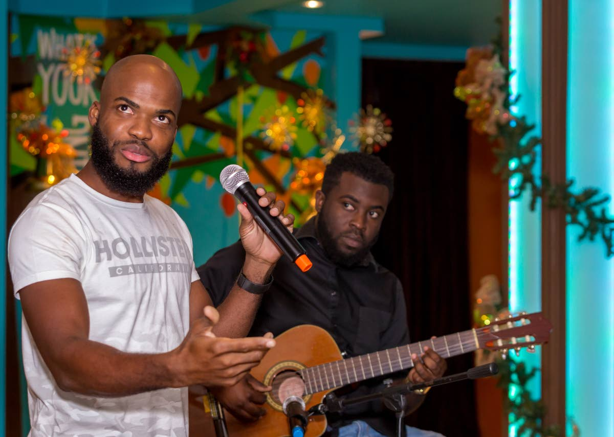 Poet Dr Kern Johnson, left, at an Open Mic event hosted by the Tobago Writers Guild at Apex Bar and Grill recently.