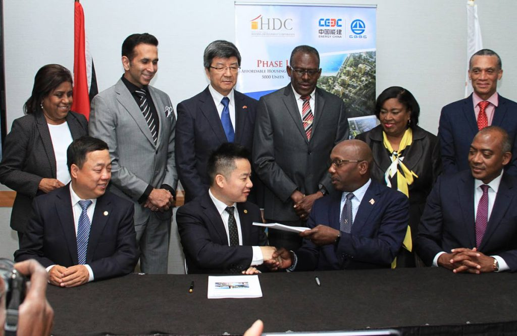 Flashback: In this May 17, 2019 file photo, front centre, China Gezhouba Group International Engineering Co Ltd (CGGC) executive vice president Zhou Xing and HDC chairman Newman George exchange documents after signing documents for phase one of 5,000 houses at Hyatt Regency, Port of Spain. At front left is CGGC president Liu Huailiang and HDC managing director Brent Lyons, front right. At back from left are Trade and Industry Minister Paula Gopee-Scoon, Attorney General and San Fernando West MP Faris Al-Rawi, China's Ambassador Song Yumin, Housing Minister Edmund Dillon, Port of Spain South MP Marlene McDonald and Minister of Foreign and Caricom Affairs Dennis Moses.