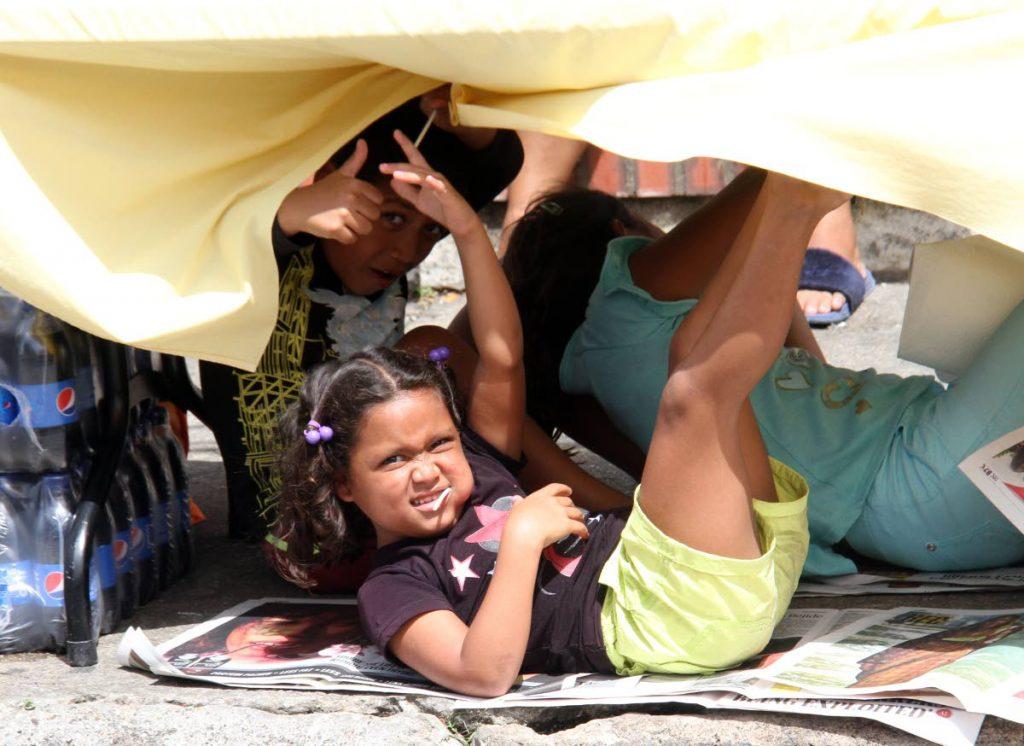En esta foto de archivo del 14 de junio de 2019, los niños venezolanos juegan debajo de una mesa frente al Queen's Park Oval, Puerto España.