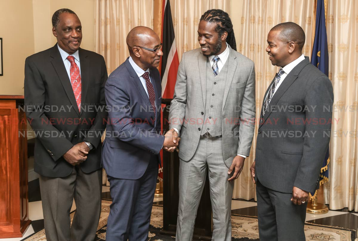 Minister of Public utilities Robert Le Hunte welcomes new parliamentary secretary in ministry of Public utilities Adrian Leonce also in photo MP Brigadier General Ancil Antoine (Ret.) at left and right senator Foster Cummings at Presidents House, St Anns on August 14.  Photo: JEFF K MAYERS