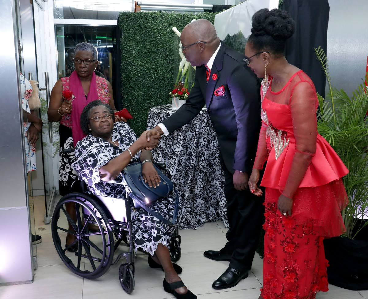 Chief Secretary Kelvin Charles, second from right, and his wife, Catherine Anthony-Charles, right, greet Kenetta Bobb, in wheelchair, and Visa Romeo-Guy at an Independence day reception in Scarborough on Thursday.