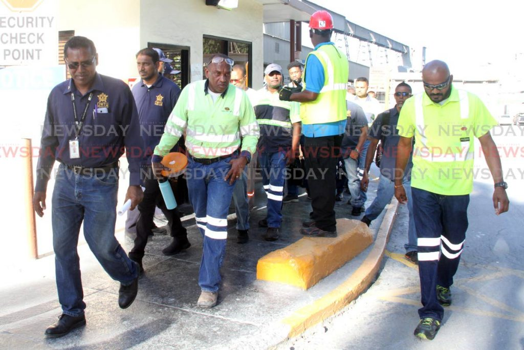 OWTU Branch President Ahmad Mohammed of Trinidad Cement Ltd, Claxton Bay, left, leads the protestesting employees as they walk pass the security booth at the main gate after refusing breathlyser tests on Monday. PHOTO BY VASHTI SINGH