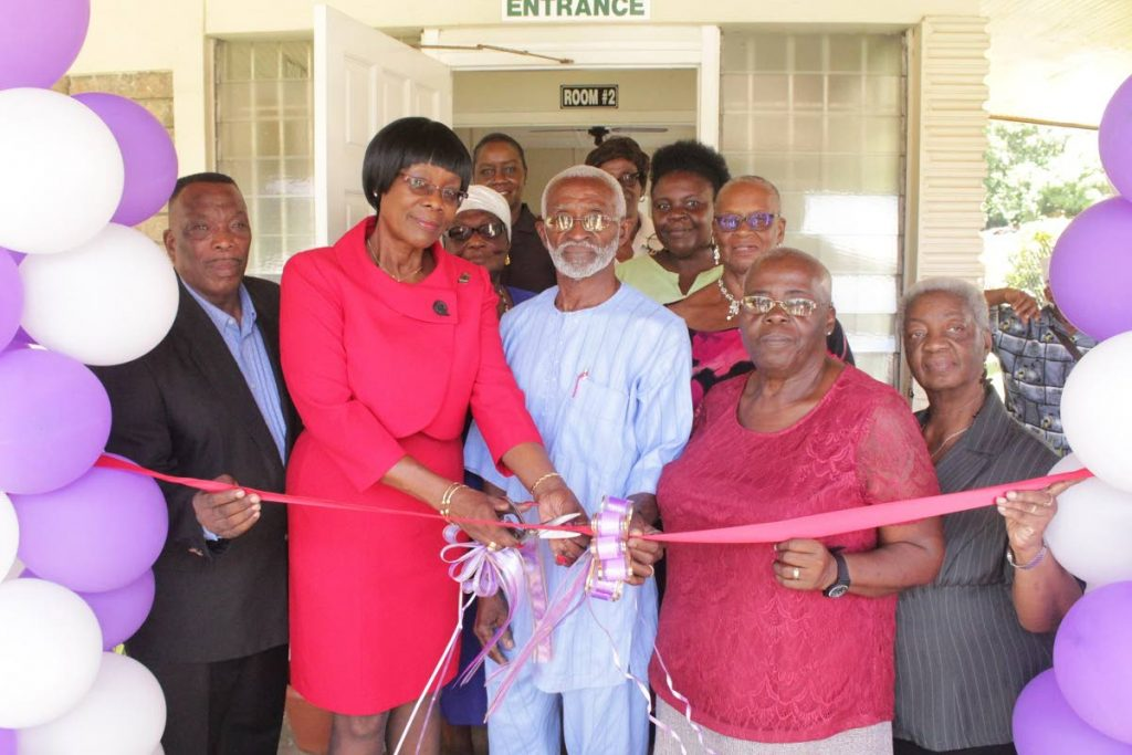 Completing the Re-Commissioning. Councillor Dr. Agatha Carrington (2nd from left) and Mr. Rudolph Hypolite (c) cut the ribbon with other members of TATE signalling the formal re-commissioning of the Rockley Vale Senior Citizens Activity Centre.