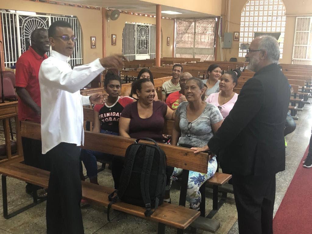 El padre Robert Christo, a la izquierda, habla con el obispo venezolano Jaime José Villarroel Rodríguez durante una visita reciente a la iglesia en Penal.
