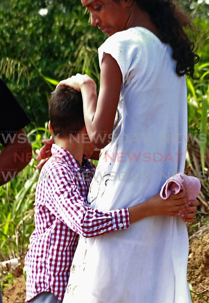 Son of the late Harricharan Ramsundar is embraced at funeral service at their home in Phulo Drive, La Brea Trace, Siparia. PHOTO BY: MARVIN HAMILTON