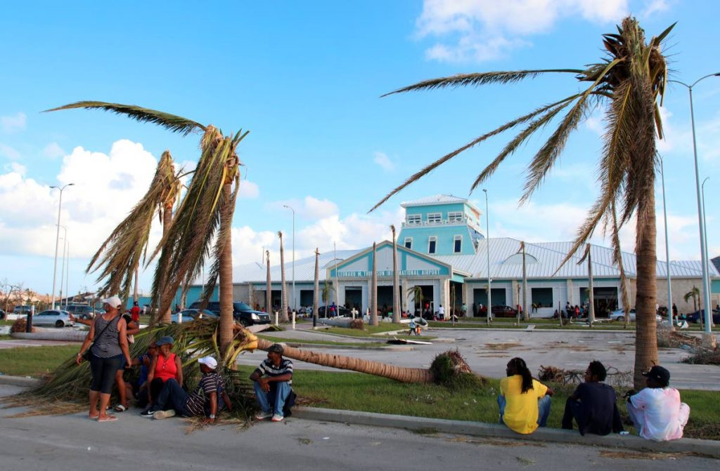 People sit under broken palm trees outside the Leonard M Thompson International Airport after the passing of Hurricane Dorian in Marsh Harbour, Abaco Islands, Bahamas, September 5. AP PHOTO