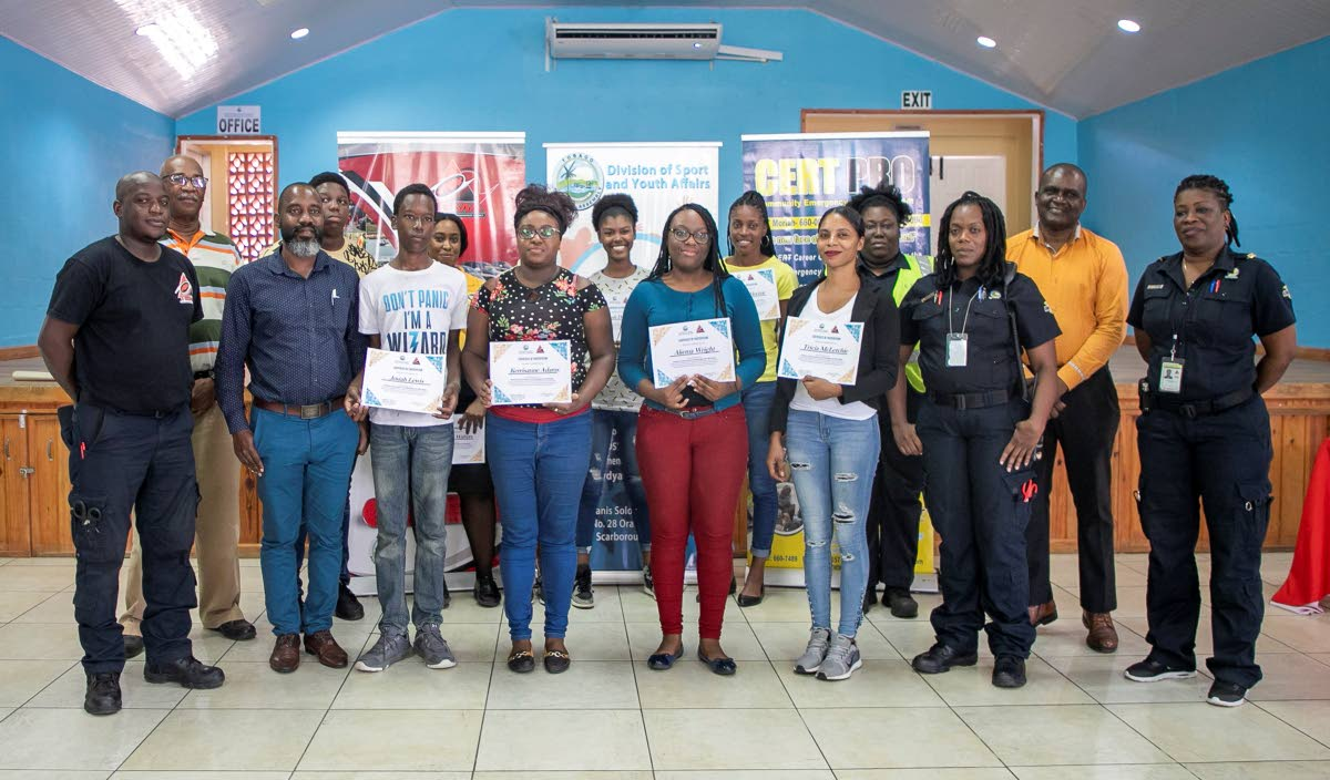 Participants in the disaster preparedness and management workshop with their certificates at the Calder Hall Multi-purpose Facility. They are flanked by staff of the Tobago Emergency Management Agency (TEMA), including its director Allan Stewart (left) and Youth Development Officer II in the Department of Youth Affairs Lyndon Wilson (front row, second from right).