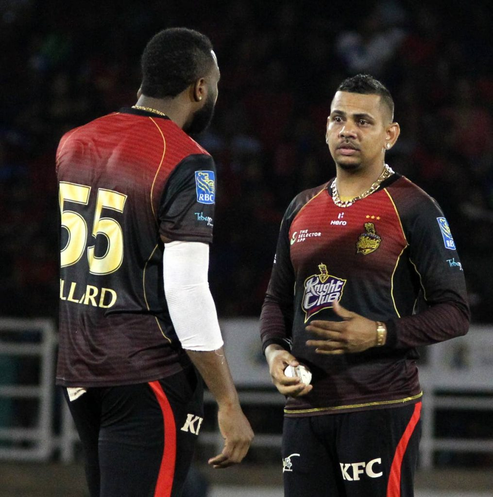 Trinbago Knight Riders captain Kieron Pollard (left) speaks to Sunil Narine during Friday's match against the Jamaica Tallawahs. PHOTO BY ROGER JACOB.