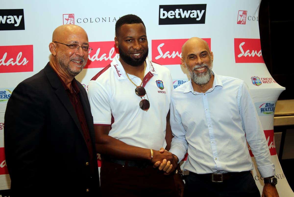 Newly-appointed West Indies T20  and ODI captain Kieron Pollard,centre, is all smiles during a Cricket West Indies media conference,held on Monday, at the Hilton Trinidad, St Ann's to announce the new captaincy. At left, CWI president Ricky Skerritt and CWI cricket ambassador Jimmy Adams,right, look on.