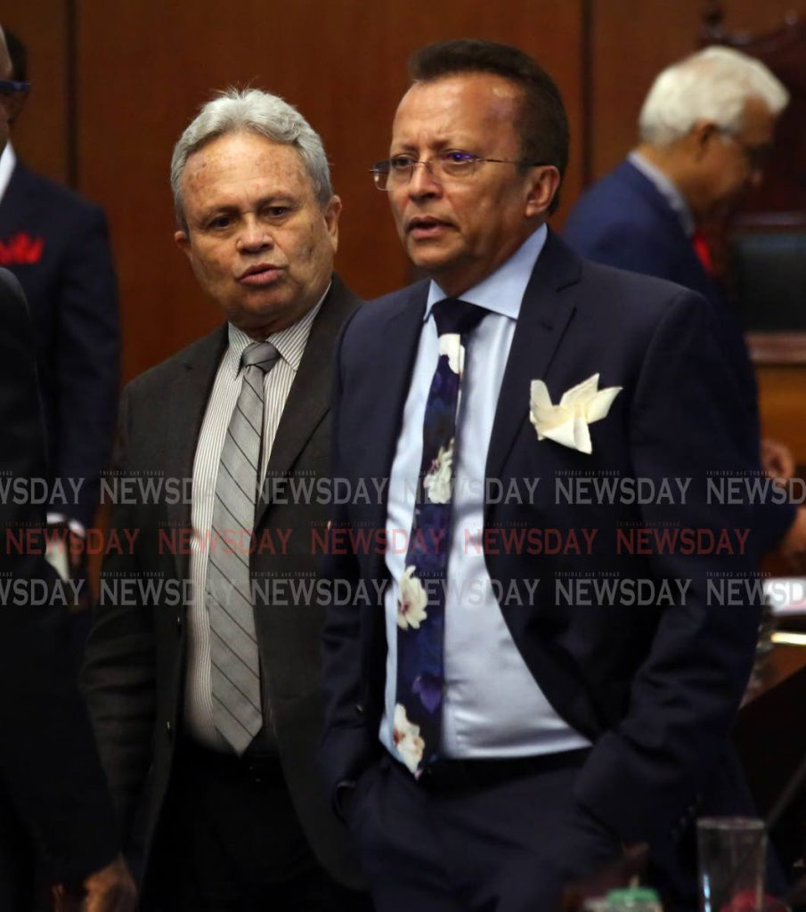 Finance Minister Colm Imbert, left, and Opposition MP Ganga Singh during a break in Parliament on September 9.   PHOTO BY SUREASH CHOLAI