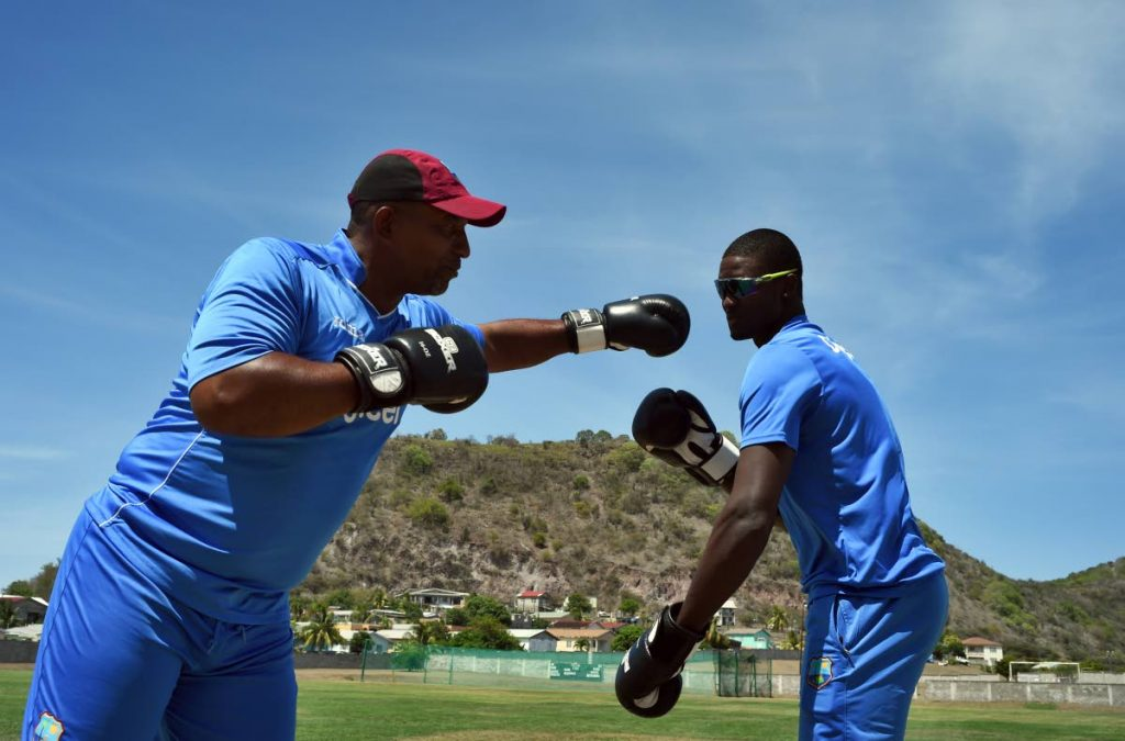 In this file photo, then West Indies cricket team captain Jason Holder (R) and former coach Phil Simmons playfully box to pay their respect to late boxer Muhammad Ali during a practice session in Basseterre, Saint Kitts, on June 10, 2016.